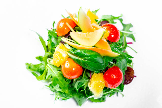 Salad with herbs, tomatoes, orange and avocado. Top view
