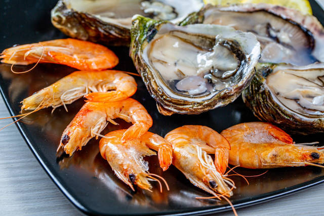 Close Up Food Photo of Fresh Shrimps and Oysters on Black Plate