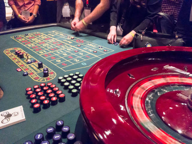 Roulette Table and Roulette Wheel in a Casino with People betting on numbers