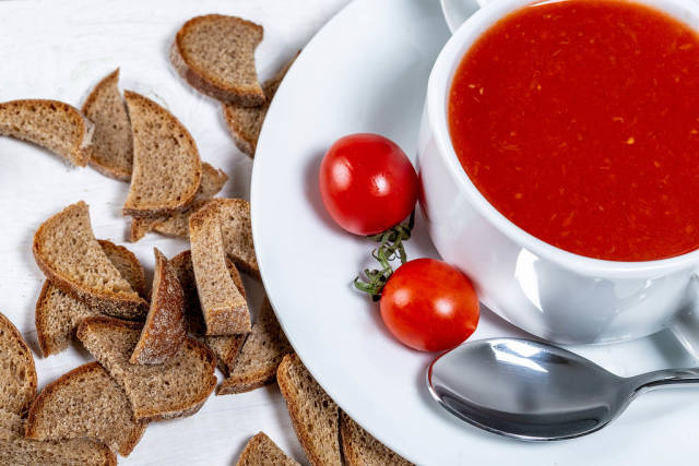 Tomato soup in a tureen with slices of black bread and tomatoes