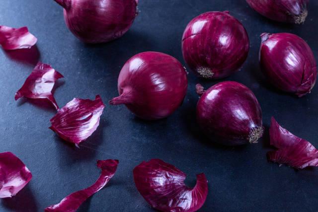 Fresh raw red onion on black table