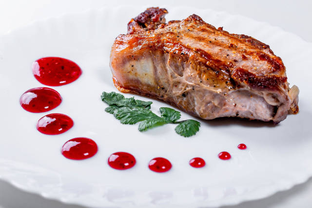 Roast meat with red sauce on a white plate
