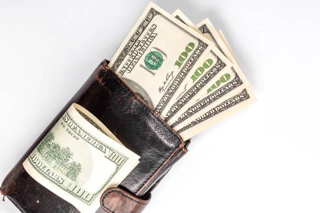 Black wallet with money inside and dollar bills on top on white background