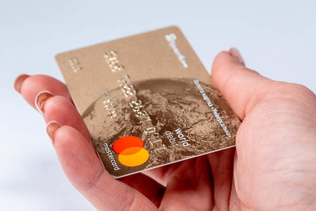Plastic card in women hand on white background
