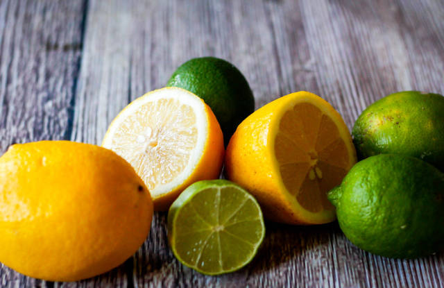 Close Up Photo of Halved and Whole Limes and Lemons on Wooden Background