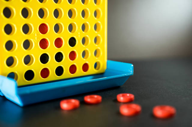 Close Up Photo of Connect Four Game on Dark Background