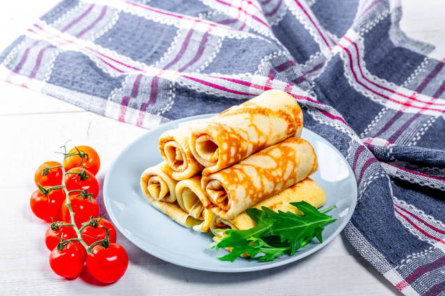 Delicious pancakes on a plate with cherry tomatoes