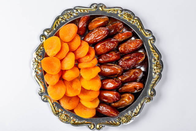 Dates and dried apricots on a tray on a white background. Top view