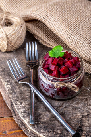 Boiled beet cubes in a glass jar on a wooden background with burlap and forks