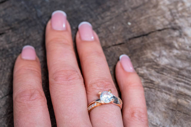 Gold ring on womans finger on old wooden background