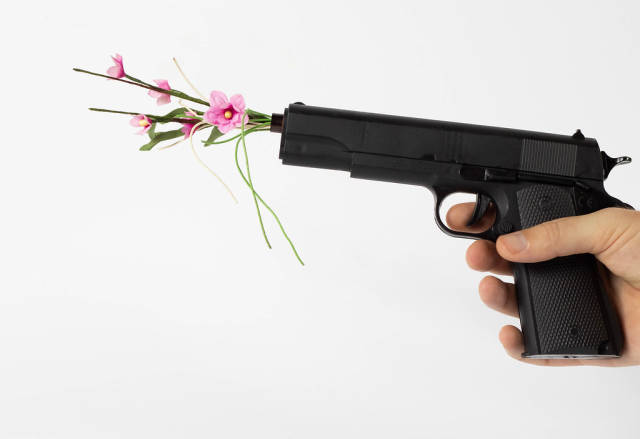 Person holding a Gun with Flowers coming out of the Gun with White Background
