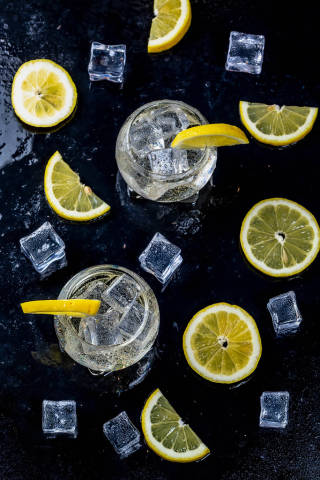 Lemonade with ice cubes and sliced lemon on black background. Top view