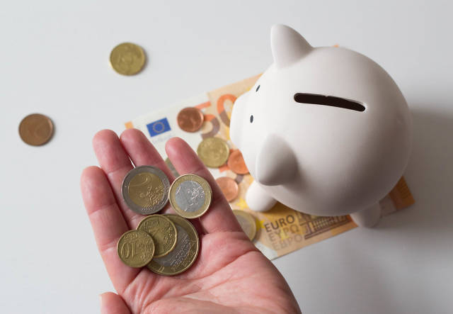 Person holding Euro Coins next to a Piggy Bank standing on Euro Banknotes on White Background