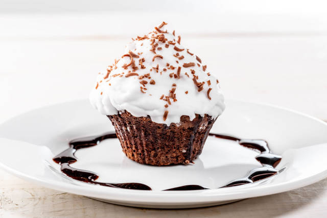 Appetizing chocolate muffin with white cream