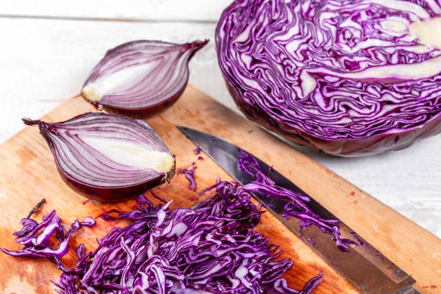 Purple cabbage and onion cut into the kitchen Board
