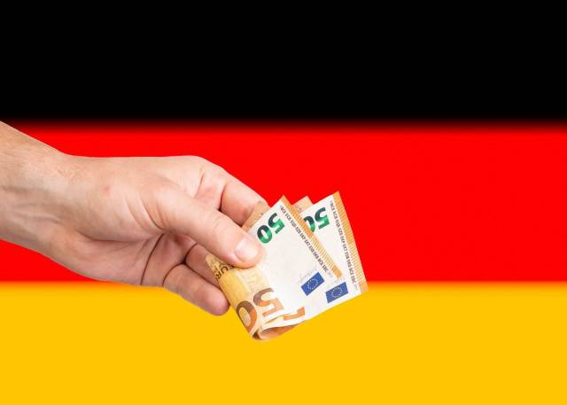 Hand with Euro banknotes over flag of Germany