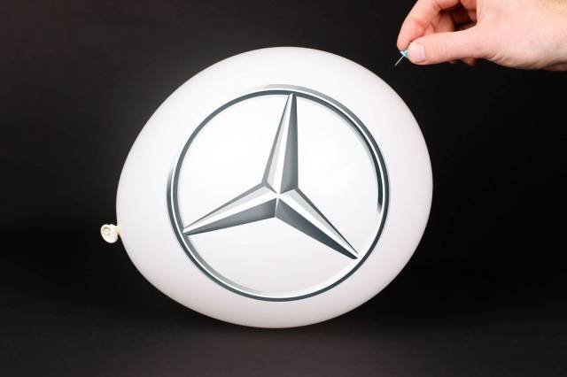Hand uses a needle to burst a balloon with Mercedes Benz logo