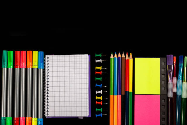 Office supplies on black background, top view