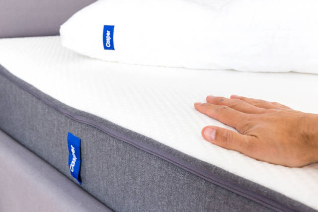 Flat hand lays on white and grey Casper mattress with memory foam, which relieves the body during sleep.