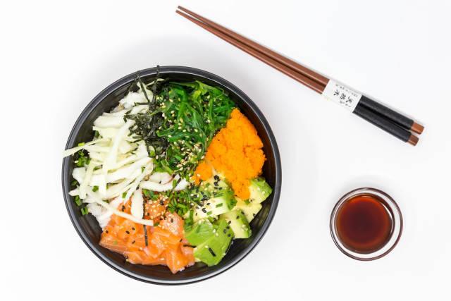 Top view - Poke Bowl Salmon Teriyaki  - with sushi rice, salmon, avocado, cabbage, wakame, wasago, nori, teriyaki-sauce, soy-sauce, sesame and chives in a bowl with chopsticks