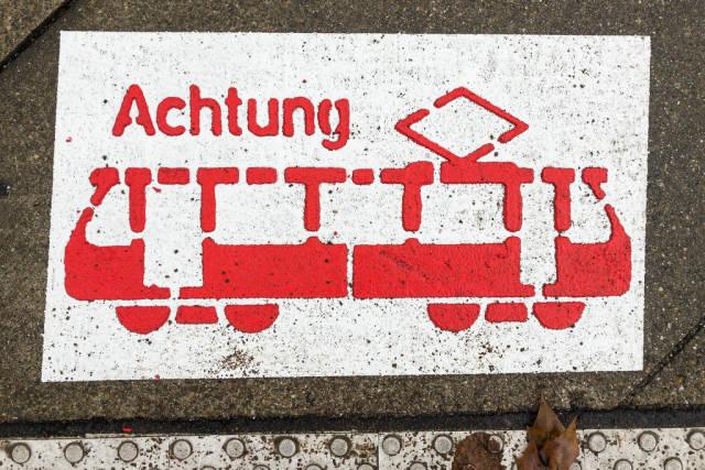 Achtung Straßenbahn Zeichen auf dem Asphalt