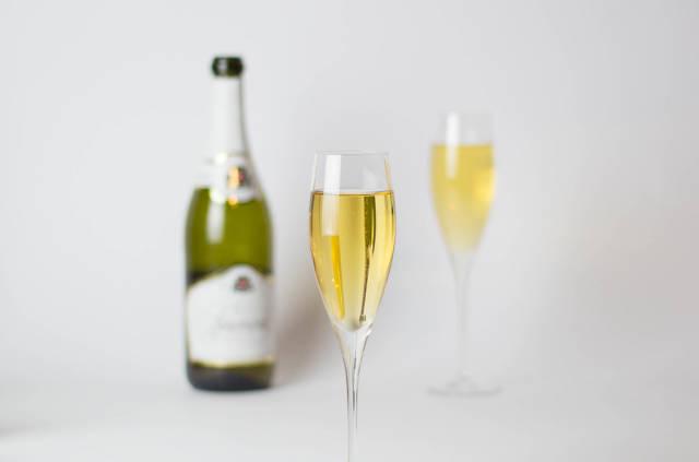 Champagnerglas und Flasche im Hintergrund