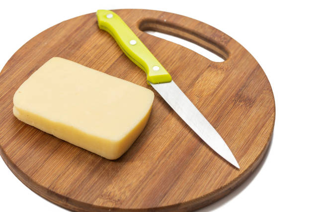 Slice of yellow cheese on the kitchen wooden board with knife