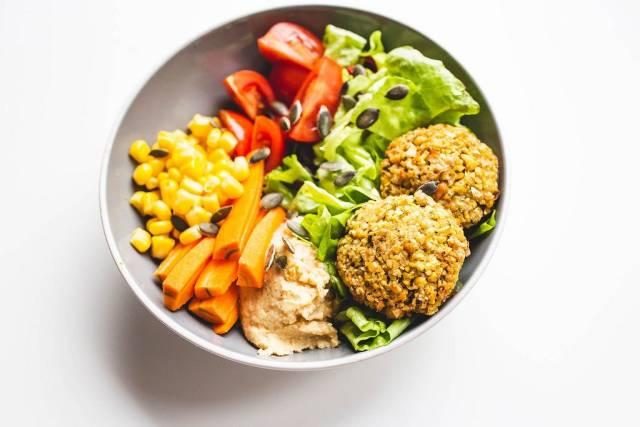 Veganes Gericht mit Falafel, Humus, Salat, Karotten, Tomaten, Mais und Sonnenblumenkernen