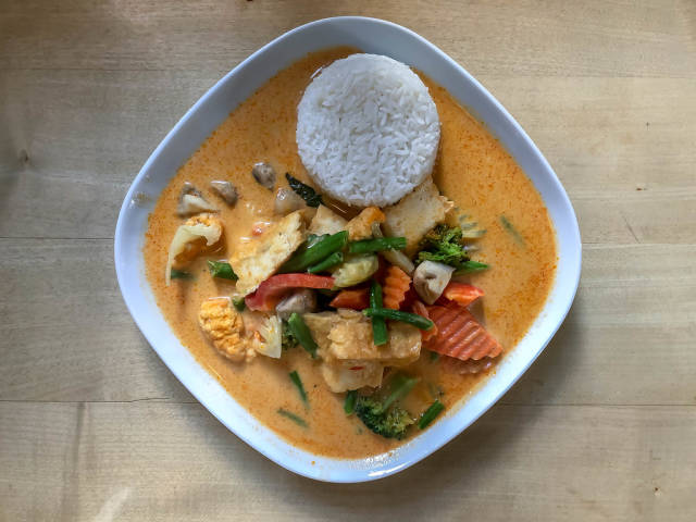 Asiatisches Mittagessen mit scharfer Tofu Thai Currysauce, Reis, frischem Gemüse, Milch, Kokosmilch und Sahne