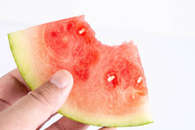 Sliced Watermelon in the hand above white background