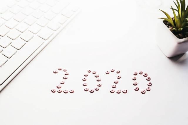 2020 geschrieben auf weißem Hintergrund mit Tastatur und Pflanze