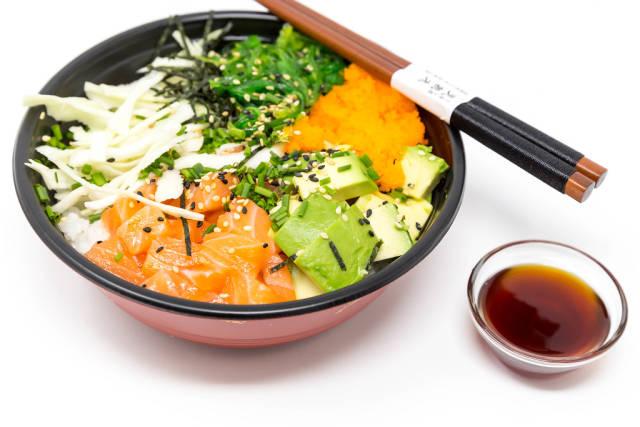 Poke Bowl Salmon Teriyaki  - with sushi rice, salmon, avocado, cabbage, wakame, wasago, nori, teriyaki-sauce, soy-sauce, sesame and chives in a bowl with chopsticks