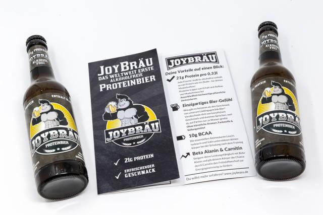 Zwei Flaschen liegend mit Broschüre - Joy Bräu weltweit erstes Alkoholfreies Proteinbier mit hohem Eiweißanteil, BCAA und Carnitin auf weißem Hintergrund