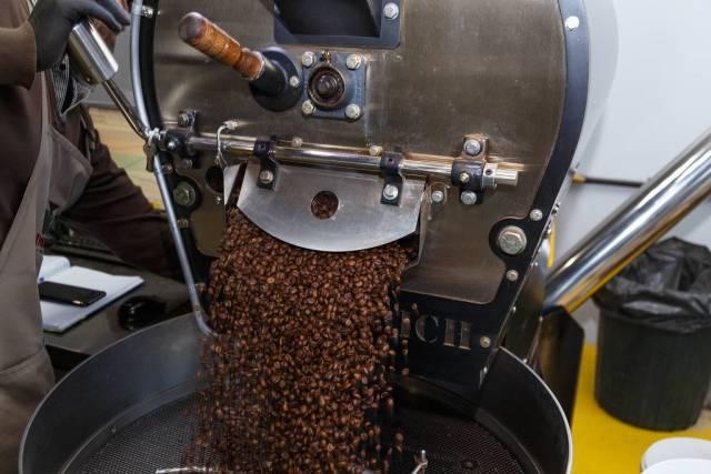 Diedrich-Maschine schüttet ganze Kaffeebohnen auf ein großes Sieb zum Mahlen