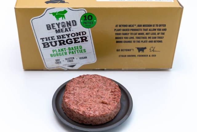 Beyond Meat Patty - eine vegane, glutunfreie Alternative zum Burger-Fleisch - auf schwarzem Teller mit der Packung im Hintergrund