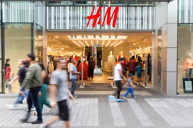 Passanten laufen an einer H&M Filiale vorbei