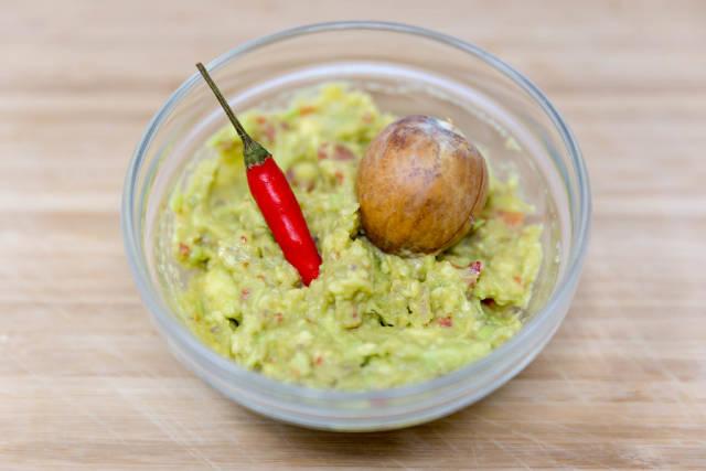 Guacamole Avocado Dip - Brotaufstrich in Schälchen mit roter Chili und Aocadokern