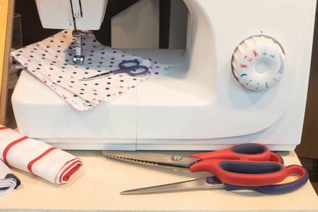 Nähmaschine, Scheren und Stoff