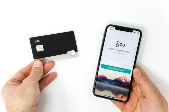 Schwarze N26 Bankkarte mit der Login-Seite des N26 Mobil-Applikations zeigt an einem iPhone