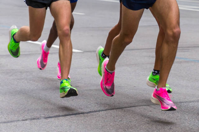 Legs of marathon runners wearing Nike ZoomX Vaporfly Next% running shoes in the pink and green versions