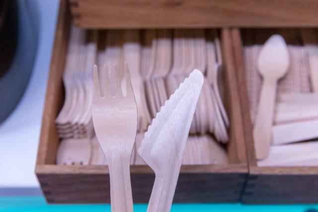 Umweltfreundliches Einwegbesteck wie Messer und Gabel aus Holz vor Kiste mit weiterem Besteck