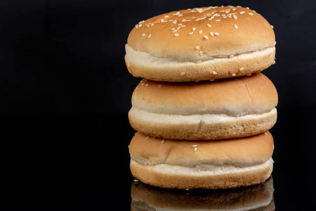 Hamburger Buns above black reflective background with copy space