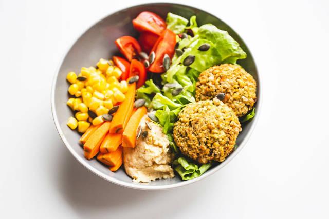 Falafel and vegetables vegan bowl on white background