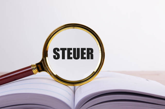 Magnifying glass and book with Steuer text
