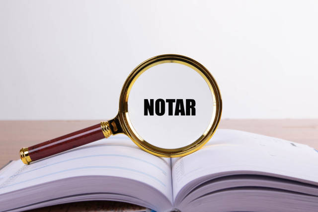 Magnifying glass and book with Notar text