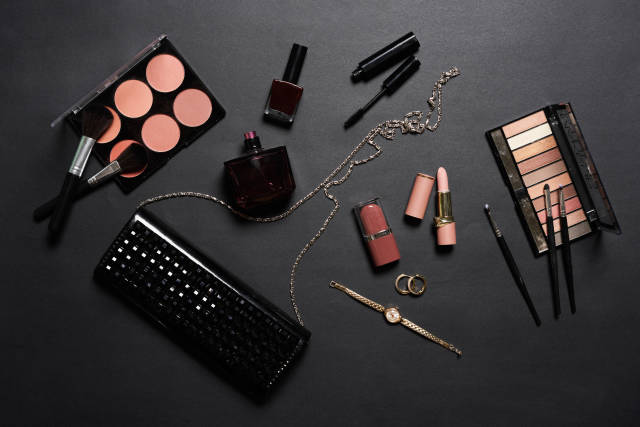 Stylish females clutch with beauty make-up products on dark background