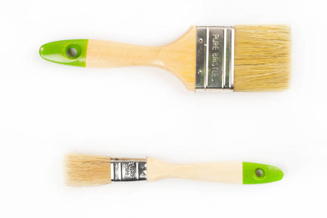 Top view, large and small wooden brushes on white