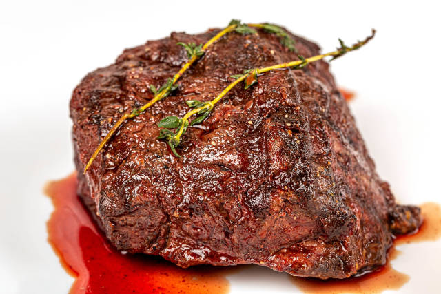 Close-up filet mignon with sauce and a sprig of thyme