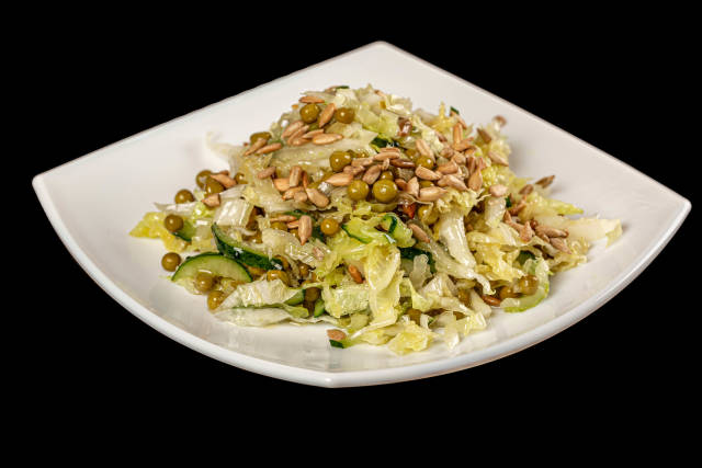 Fresh salad with sunflower seeds, chinese cabbage, peas and cucumbers