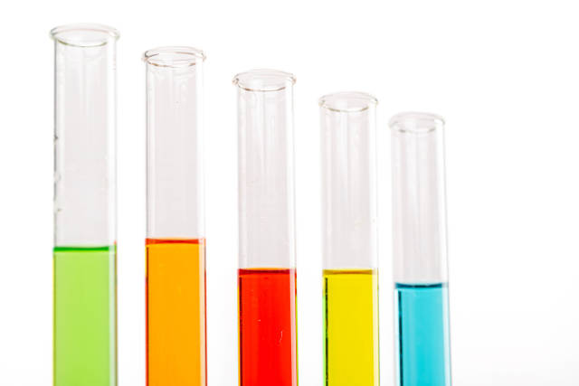 Colored liquids in five test tubes over white background